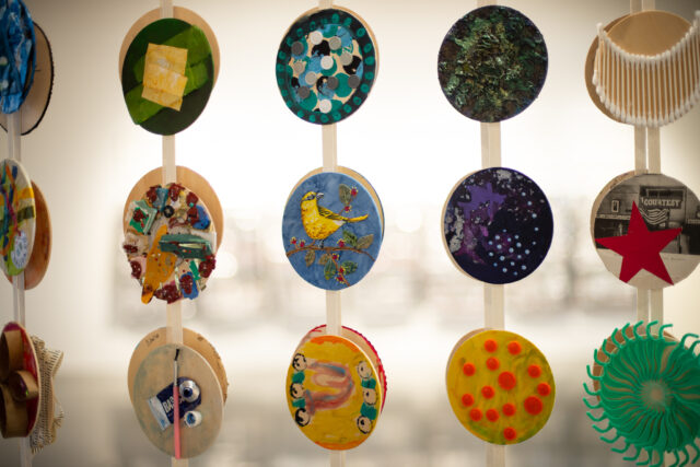 hanging strings with glued circles that show different art work on each one, three circles glued per string.